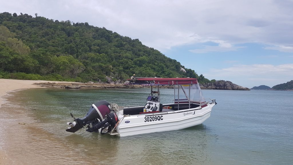 A 6 m white boat with an outboard motor is backed onto a beach.