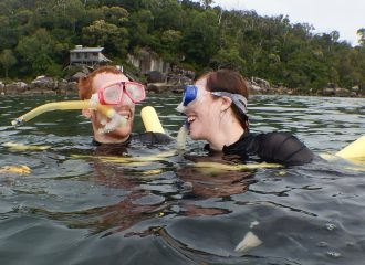 Two caucasian people smiling at each other while snorkelling