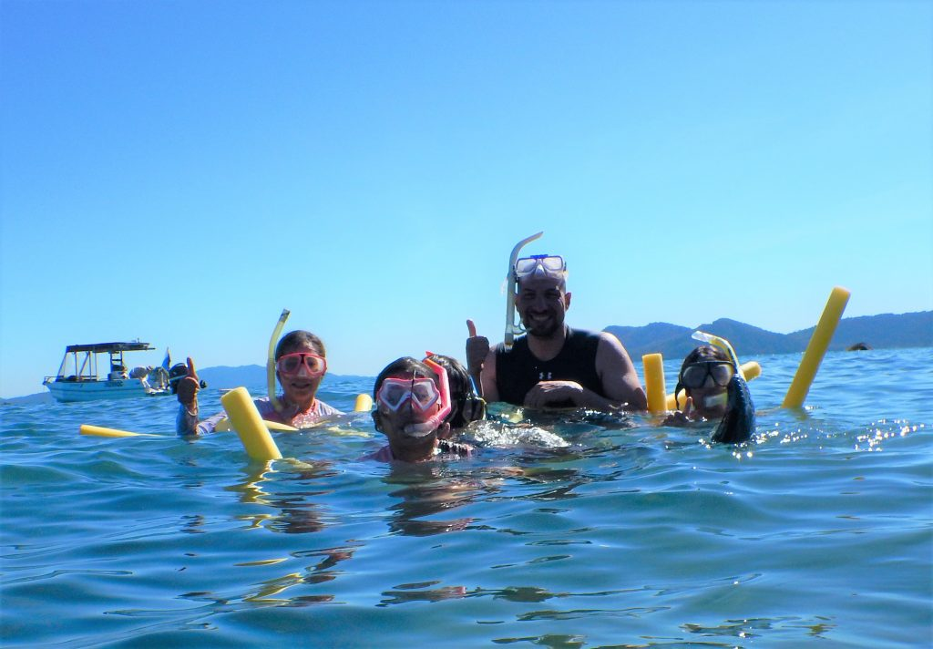 A family floats in a tropical sea with snorkelling gear giving the thumbs up