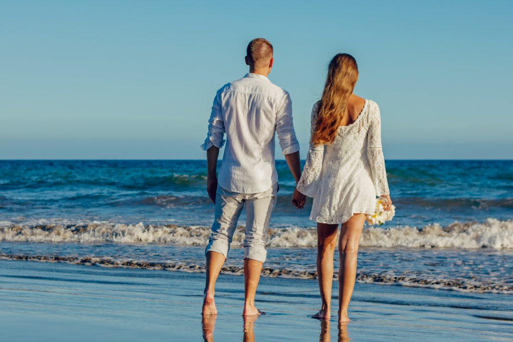 A couples holds hands as they walk along a deserted beach